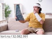 Купить «Young man after accident recovering at home», фото № 32082991, снято 3 мая 2019 г. (c) Elnur / Фотобанк Лори