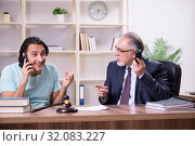 Young man visiting experienced male lawyer. Стоковое фото, фотограф Elnur / Фотобанк Лори