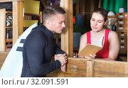 Купить «Happy athletic man talking to girl at reception», фото № 32091591, снято 30 апреля 2018 г. (c) Яков Филимонов / Фотобанк Лори
