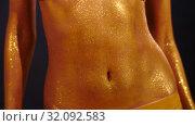 Belly of a dancing woman with golden skin. Стоковое видео, видеограф Илья Шаматура / Фотобанк Лори