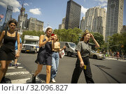 Distracted millennials, engrossed in a smartphone, cross West 23rd Street in New York on Thursday, July 25, 2019. (© Richard B. Levine). Редакционное фото, фотограф Richard Levine / age Fotostock / Фотобанк Лори