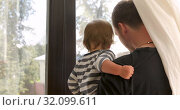 Anonymous father and baby looking out window. Стоковое видео, видеограф Ekaterina Demidova / Фотобанк Лори