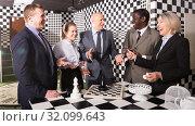 Smiling businesspeople solving together conundrums. Стоковое фото, фотограф Яков Филимонов / Фотобанк Лори