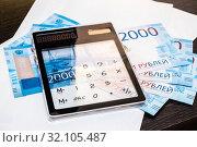 Деньги Российской Федерации, конверты и прозрачный калькулятор на фоне темного стола. Стоковое фото, фотограф Кузин Алексей / Фотобанк Лори
