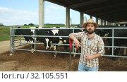 Купить «Smiling man farmer standing near cow on background at farm outdoor», видеоролик № 32105551, снято 9 июня 2019 г. (c) Яков Филимонов / Фотобанк Лори