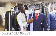 Afro-american man seller is showing jacket and tie in shop. Стоковое видео, видеограф Яков Филимонов / Фотобанк Лори