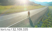 Купить «Flight over hitchhiker tourist walking on asphalt road. Huge rural valley at summer day. Backpack hiking guy.», видеоролик № 32109335, снято 2 августа 2018 г. (c) Александр Маркин / Фотобанк Лори