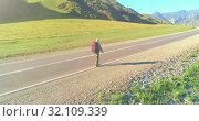 Купить «Flight over hitchhiker tourist walking on asphalt road. Huge rural valley at summer day. Backpack hiking guy.», видеоролик № 32109339, снято 2 августа 2018 г. (c) Александр Маркин / Фотобанк Лори