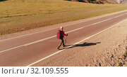 Купить «Flight over hitchhiker tourist walking on asphalt road. Huge rural valley at summer day. Backpack hiking guy.», видеоролик № 32109555, снято 7 августа 2018 г. (c) Александр Маркин / Фотобанк Лори