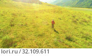 Купить «Flight over Backpack hiking tourist walking across green mountain field. Huge rural valley at summer day.», видеоролик № 32109611, снято 12 августа 2018 г. (c) Александр Маркин / Фотобанк Лори
