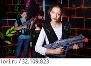 Купить «Cheerful teen girl standing with laser pistol in dark lasertag room during game with friends», фото № 32109823, снято 24 октября 2018 г. (c) Яков Филимонов / Фотобанк Лори