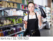 Female hairdresser in apron holding blow dryer and hair cutters. Стоковое фото, фотограф Яков Филимонов / Фотобанк Лори