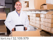 Купить «Mature male worker standing with cart at workplace», фото № 32109979, снято 22 апреля 2017 г. (c) Яков Филимонов / Фотобанк Лори