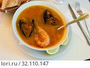 Купить «Hot seafood soup with prawns, mussels and vegetables served», фото № 32110147, снято 20 ноября 2019 г. (c) Яков Филимонов / Фотобанк Лори