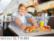 Купить «Fat woman eating high calorie food in mall», фото № 32110883, снято 24 мая 2019 г. (c) Tryapitsyn Sergiy / Фотобанк Лори