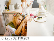 Little girl washing dishes near tired housewife. Стоковое фото, фотограф Tryapitsyn Sergiy / Фотобанк Лори