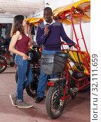 Купить «African American driver of bikecab offering tour of city to young woman», фото № 32111659, снято 22 мая 2018 г. (c) Яков Филимонов / Фотобанк Лори