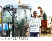 Positive African American man standing near farm tractor in vineyard outdoor. Стоковое фото, фотограф Яков Филимонов / Фотобанк Лори