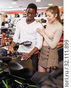 Portrait of young smiling man and woman looking new motorbike at motosalon showroom. Стоковое фото, фотограф Яков Филимонов / Фотобанк Лори