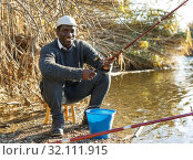 Купить «Fisherman sitting on wooden stool», фото № 32111915, снято 27 января 2019 г. (c) Яков Филимонов / Фотобанк Лори