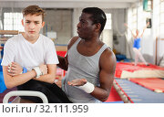 Купить «Male coach talking with upset teenage boy on gymnastic equipment at acrobatic center», фото № 32111959, снято 17 января 2019 г. (c) Яков Филимонов / Фотобанк Лори