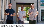 Купить «male friends with earphones running outdoors», видеоролик № 32112535, снято 27 июля 2019 г. (c) Syda Productions / Фотобанк Лори