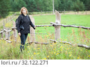 Купить «Hiking traveller stands in rural paddock with binoculars and backpack, European woman looking at camera, wooden fence as copyspace», фото № 32122271, снято 11 августа 2019 г. (c) Кекяляйнен Андрей / Фотобанк Лори