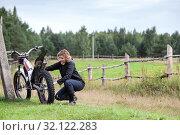 Middle age woman trying to repair her motorcycle, countryside road in farmland, copy space. Стоковое фото, фотограф Кекяляйнен Андрей / Фотобанк Лори