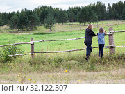 Купить «Adult woman and teenage girl enjoying nature in countryside, standing close to farm pasture, rear view, copyspace», фото № 32122307, снято 11 августа 2019 г. (c) Кекяляйнен Андрей / Фотобанк Лори
