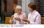 Купить «senior women eating takeaway food on city street», видеоролик № 32123067, снято 25 августа 2019 г. (c) Syda Productions / Фотобанк Лори