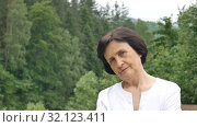 Female portrait of dissatisfied upset older woman with short dark hair and wrinkled face looking at the camera with disapproval outdoors on mountain hill with green forest on background. Стоковое видео, видеограф Ольга Балынская / Фотобанк Лори