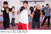 Cheerful sportsmen practicing boxing punches. Стоковое фото, фотограф Яков Филимонов / Фотобанк Лори
