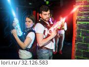 Купить «Man and woman back to back in laser beams», фото № 32126583, снято 25 апреля 2018 г. (c) Яков Филимонов / Фотобанк Лори