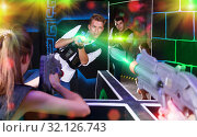 Excited people playing enthusiastically laser tag game. Стоковое фото, фотограф Яков Филимонов / Фотобанк Лори