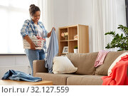 Купить «happy woman picking clothes for laundry at home», фото № 32127559, снято 7 апреля 2019 г. (c) Syda Productions / Фотобанк Лори