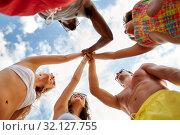 Купить «friends making high five over sky on summer beach», фото № 32127755, снято 29 июля 2018 г. (c) Syda Productions / Фотобанк Лори