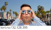 Купить «surprised man in sunglasses over venice beach», фото № 32128395, снято 22 июля 2015 г. (c) Syda Productions / Фотобанк Лори