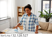 Купить «african american woman ironing bed linen at home», фото № 32128527, снято 7 апреля 2019 г. (c) Syda Productions / Фотобанк Лори