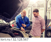 Купить «auto mechanic with clipboard and man at car shop», фото № 32128567, снято 1 июля 2016 г. (c) Syda Productions / Фотобанк Лори
