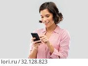 Купить «young woman in striped shirt using smartphone», фото № 32128823, снято 6 марта 2019 г. (c) Syda Productions / Фотобанк Лори