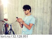 Купить «man with smartphone and fixed gear bike on street», фото № 32128951, снято 15 июня 2016 г. (c) Syda Productions / Фотобанк Лори