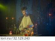 Купить «portrait of wizard with burning candles and magic potions», фото № 32129243, снято 14 августа 2019 г. (c) Майя Крученкова / Фотобанк Лори