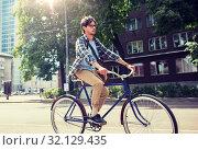 Купить «young hipster man with bag riding fixed gear bike», фото № 32129435, снято 15 июня 2016 г. (c) Syda Productions / Фотобанк Лори