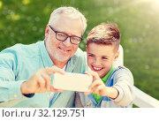 Купить «old man and boy taking selfie by smartphone», фото № 32129751, снято 9 июля 2016 г. (c) Syda Productions / Фотобанк Лори