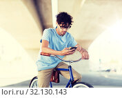 Купить «man with smartphone and earphones on bicycle», фото № 32130143, снято 15 июня 2016 г. (c) Syda Productions / Фотобанк Лори
