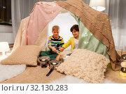 Купить «boys with pots playing music in kids tent at home», фото № 32130283, снято 18 февраля 2018 г. (c) Syda Productions / Фотобанк Лори