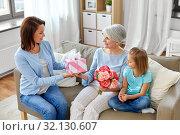 Купить «family giving present and flowers to grandmother», фото № 32130607, снято 5 мая 2019 г. (c) Syda Productions / Фотобанк Лори