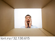 Купить «shocked man looking into open parcel box», фото № 32130615, снято 9 мая 2019 г. (c) Syda Productions / Фотобанк Лори