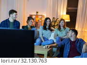 Купить «happy friends watching tv at home in evening», фото № 32130763, снято 22 декабря 2018 г. (c) Syda Productions / Фотобанк Лори