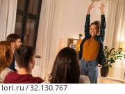 Купить «happy friends playing charades at home in evening», фото № 32130767, снято 22 декабря 2018 г. (c) Syda Productions / Фотобанк Лори